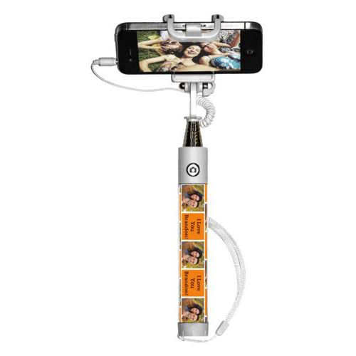 "Personalized selfie stick personalized with a photo and the saying ""I Love You Brandon!"" in black and juicy orange"